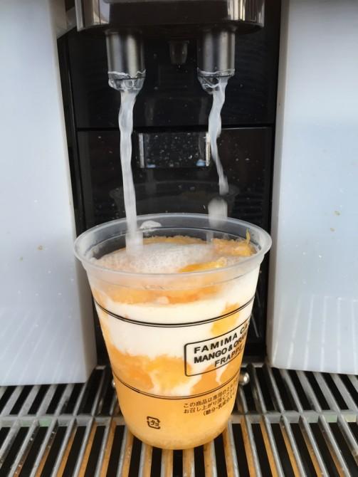 ファミマのマンゴー&オレンジフラッペを制作中(ホットミルク注入中)