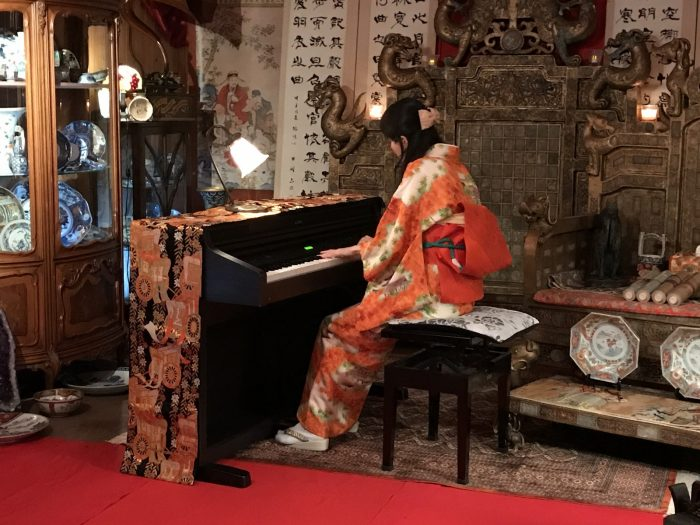 ピアノを弾く着物の女性